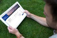 Mann sieht auf Bildschirm eines Tablets
