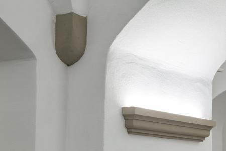 Das sandsteinfarbene Capapor Sonderprofil mit indirekter Beleuchtung kaschiert den Übergang vom Sanierputz im unteren Wandbereich zum Akustiksystem CapaCoustic Fine oberhalb, Fotos: Willi Fuchs Fotografie