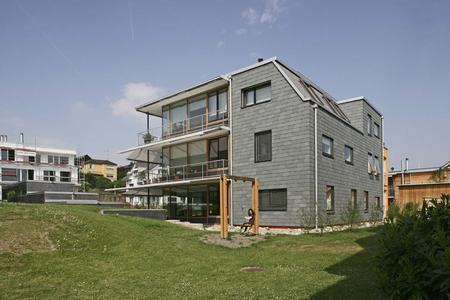 Die Nord- und Ostflächen des Gebäudes zeigen sich zurückhaltend und eher geschlossen. Hier dominiert die grüne Schieferfassade