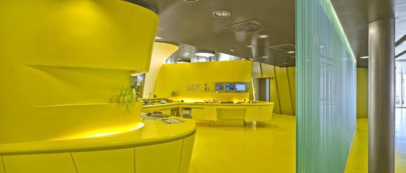 Geschwungene Formen und gelbe Farbe prägen auch den Empfangstresen. Foto: Caparol Farben Lacke Bautenschutz/Martin Duckek