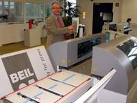 Hans-Joachim Bellers, responsible for the BEIL system business demonstrating the inline/online system for web printing in the new customer centre of the company in Abensberg. In the background is the Mutiformat-Hybrid bender.