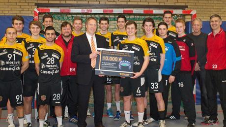 Alexander Bahlmann überreicht einen Scheck über 10.000 EUR an die Handballer vom TSV Anderten