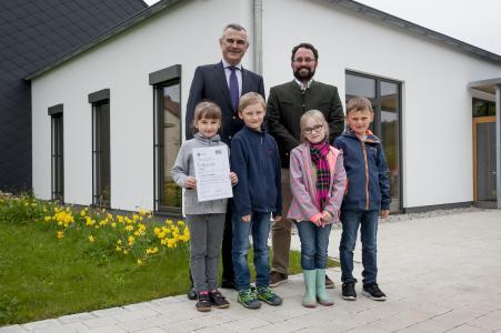 Horst Schneider, Vorstand der TÜV SÜD Stiftung, mit Lehrer Matthias Brendel von der Grundschule Oberhausen und seinen Schülern
