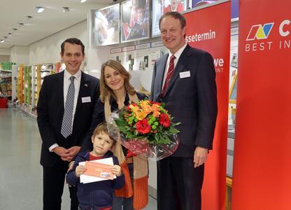 Die dm-Kundin Annika Schwoll (2. von rechts) aus Düsseldorf hat das zwanzigmillionste CEWE FOTOBUCH in Auftrag gegeben und freut sich nun auf eine Flugreise für zwei Personen mit der CEWE AIR aus der TUIfly-Flotte