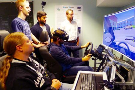 Artur Barz benutzt den Fahrsimulator mit der VR-Brille, neben ihm sitzt Tobias Puderer. Das Experiment beobachten Prof. Jan Conrad, Andreas Weisenberg und Patrick Schmitt (von links). Foto: Susanne Lilischkis