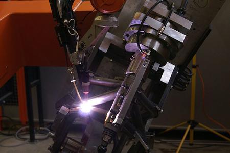 Per Kehl- und V-Nähten mit 2 mm Spaltüberbrückung schweißt ein Roboter die Motorradrahmen bei KTM wirtschaftlich mit dem System MagicWave 4000