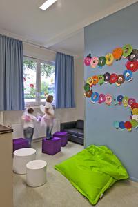"""Für die farbliche Gestaltung des Help & Hope Kidstreff nutzten die Caparol-Farbdesigner die Collagenbücher """"Lernwelten – Farbwelten"""". Die gewählte Farbwelt basiert auf Grün- und Blautönen – passend zu den violetten Sitzhockern und dem schwarzen Ledersofa, die in der Einrichtung bereits vorhanden waren, (Foto: Caparol/Help & Hope)"""