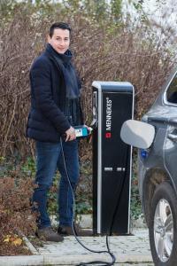 WEMAG-Projektmanager Benjamin Hintz schließt ein Elektroauto an der Ladesäule an, Foto: WEMAG/Stephan Rudolph-Kramer