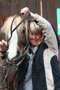 Therapiepferd Romeo wird von seiner gehörlosen Reiterin aufgetrenst (Foto: Judith Röther)