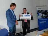 Die Fahne der Systec GmbH in Münster wird künftig von Niederlassungsleiter Jan Leideman (l.) hochgehalten. Der scheidende Geschäftsführer Tilmann Wolter über-gab ihm die Leitung des Unternehmensstandorts im Rahmen einer kleinen Zeremo-nie. (Bild: Systec GmbH)