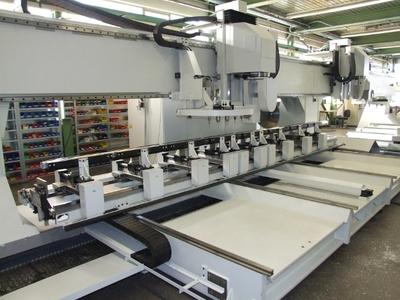 Die fast 15 m lange EiMa-Sondermaschine mit 2 Spindelköpfen. Ihre Fahrständer können auf der X-Achse bis zu 100 m/min beschleunigen. Für Bewegungen auf der Y-Achse wird der ganze Maschinentisch bewegt. Beim Beladen fährt der Tisch 3 m nach vorne