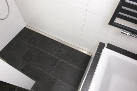 Zeitlos und praktisch – das Hauptbadezimmer im Obergeschoss eines Wohnhauses in Schloß Holte-Stukenbrock ist in Weiß-anthrazit gehalten. Die Duschrinnen-Abdeckung der Firma Richard Brink bildet einen spannenden Kontrast zu den Fliesen