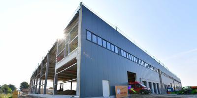 Große Teile der anthrazitfarbenen Isopaneel-Fassade sind fertiggestellt. Als nächstes folgen zudem die restlichen Türen, Tore und Fensterbänder