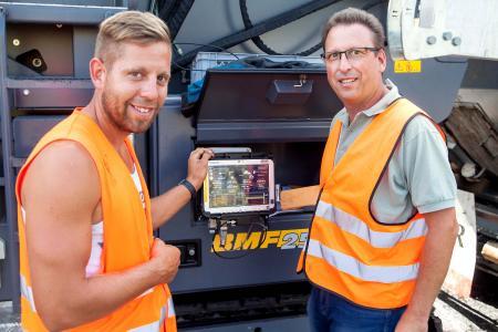 Mike Herrmann (re) und Polier Florian Bangert überprüfen die Daten an der Konsole, die am Fertiger angebracht wurde.