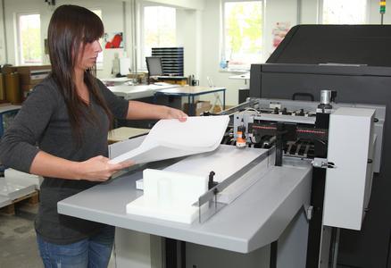 Veronika Popek legt am Langformatanleger der NexPress SX3300 Papier nach