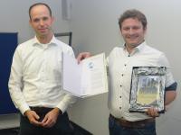 v.l.n.r.: Laudator Dr. Jan-Hendrik Oetjens von der Robert Bosch GmbH übereicht stellvertretend für das edacentrum den EDA Achievement Award 2019 an Dr. rer. nat. Alexander Viehl vom FZI Forschungszentrum Informatik