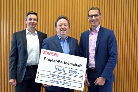 v.l.n.r.: Prof. Dr. Peter M. Rose (Hochschule Bremen) nimmt den Scheck entgegen von Jochen Bohl (Geschäftsführer, links) und Dietmar Wegers (Vertriebsleiter der STAPLES (Deutschland) GmbH, rechts)