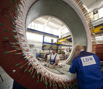 Inserting of copper coils into the stator core for an AC-machine.