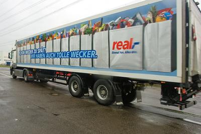 Transport und Werbung - alles mit einem LKW. Die neue Real Werbekampagne schildert mit einem Augenzwinkern Situationen aus dem täglichen Verkehrschaos
