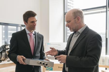 Der stellvertretende IISB-Institutsleiter Prof. Dr. Martin März (rechts), Leiter des Geschäftsbereichs Leistungselektronik, informiert Staatssekretär Stefan Müller über die Leistungsfähigkeit moderner leistungselektronischer Wandler (Foto: Fraunhofer IISB).