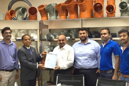 Khaisar Syed (links) überreicht der Firma Bahrain Pipes BSC die Urkunde für 10-jährige Zusammenarbeit mit dem SKZ