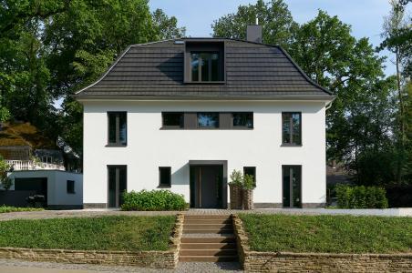 Straßenansicht: Symmetrisch angeordnete Fenster- und Türflächen strukturieren Fassade und Dach. Ein wiederkehrendes Element sind die schmalen, hochformatigen Stulpfenster (Schüco AWS 75.SI) / Bildnachweis: Schüco International KG // Fotograf: Christian Eblenkamp