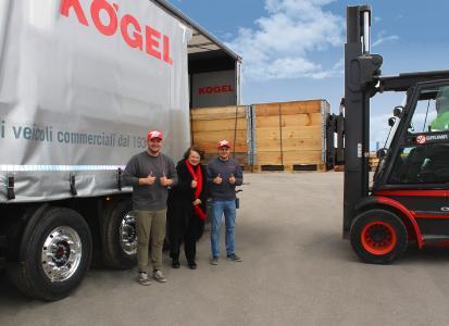 Petra Adrianowytsch, membre de la direction de Kögel, entourée des nombreux super-héros de la logistique de Kögel