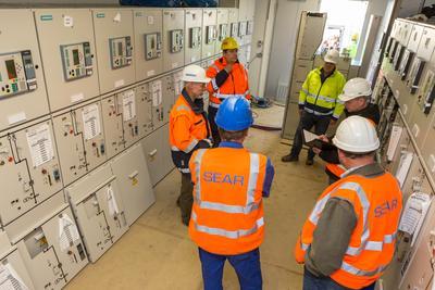 Während der Begehung informiert sich WEMAG-Projektleiter Harald Spieß (li.) in der neuen Schaltanlage bei den beauftragten Unternehmen über den aktuellen Baufortschritt / Foto: WEMAG/Rudolph-Kramer