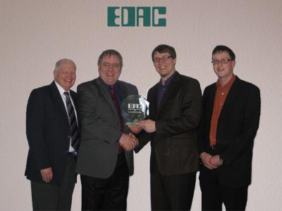 B. Raikes and A. King handing over the award to A. Engelking and T. Vosseler