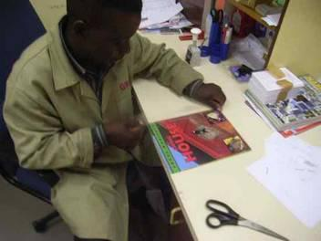 "A library employee in Namibia applying self-adhesive ""filmolux soft PP"" to books. To be able to use the film as effectively as possible and protect  a large number of books library employees first cut ""filmolux soft PP"" into strips."
