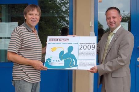 Schulleiter Hans-Jürgen Weilepp (links) und Arend Leers, Leiter des Vertriebszentrums Leipzig von STIEBEL ELTRON, bei der Übergabe des offiziellen Patenschaft-Schildes, das die Zusammenarbeit zwischen der Gerhart-Hauptmann-Regelschule und STIEBEL ELTRON.