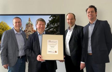 Bereichsleiter SAM, Oliver Schäpe (ganz rechts), überreicht das U-S-C SAM Zertifikat an die Verantwortlichen der Landeshauptstadt Hannover (von links nach rechts: Herr Kropp, Herr Rackow und Bereichsleiter Herr Vogel) als Compliance Nachweis für Microsoft und Wirtschaftsprüfer.