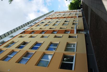 Auf der Rückseite der Mehrgeschossgebäude prägen die symmetrisch angeordneten Balkone das Erscheinungsbild. Ihre Farbgebung akzentuiert die Putzfassade
