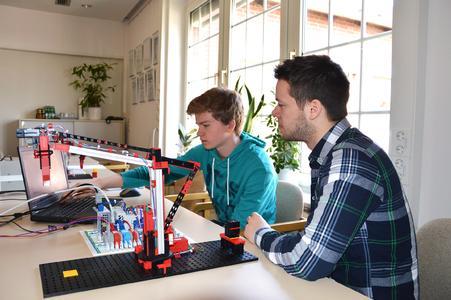 Marius Warzecha (Dualer Student Elektrotechnik) mit Lars Dittmar bei der Programmierung eines Industrie-Anlagen Modells
