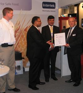 Presentation of the certificate by Dr. Kurt-Peter Raezke, Director of Testing & Analytics for Intertek Food Services (right), and Eric Wenger, Chairman for True Source Honey (left), to Prakash Kejriwal, Director of Kejriwal Bee Care India, and Amit Dhanuka, CEO for Kejriwal Bee Care India