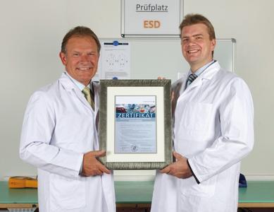 """Niels Peter Hansen (links/rechts), Geschäftsführer von Berendsen, Textilservice, nimmt das Zertifikat, """"Qualitätsgesicherte Wiederaufbereitung von ESD-Kleidung"""" von Dr. Andreas Schmidt (Hohenstein Institute) entgegen © Berendsen GmbH"""