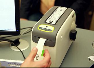 Entnahme des komfortablen Patientenarmbandes aus dem Schnellwechseldrucker HC-100. Bandwechsel zwischen Erwachsenen und z.B. Kinderbändern auf Knopfdruck (Foto: Zebra)