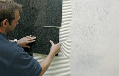Wandverlegung von Naturwerksteinplatten mit PCI Carra-light. Foto: PCI