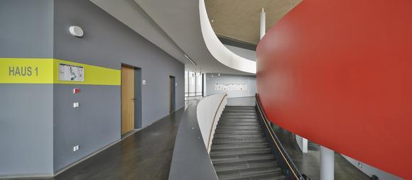 Privatgymnasium St. Leon-Rot, Echt stark: Form und Farbe prägen das Foyer der Schule. Das Rot wirkt besonders intensiv durch die vergrauten, dunklen Umgebungsfarben, Foto: Caparol Farben Lacke Bautenschutz