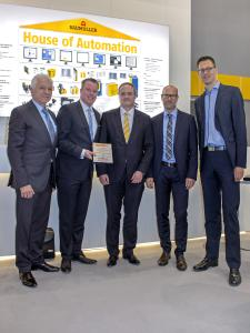 "During the presentation of the award ""Supplier of the year 2015"" at the Hannover Messe 2016, from left to right: Eugene Wojciechowski (Husky), Randy Auld (Husky), Andreas Baumüller (Baumüller), Stephan König (Husky), Roel Hoogveld (Husky)"