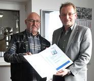 Rüdiger Loock, Fachkraft für Arbeitssicherheit der Frankenfeld Logistikgruppe (links im Bild), nimmt den Preis von Guido Stadtmann, BGHW, in Empfang