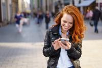 Junge Frau mit Handy, nexnet übernimmt Subscription Billing und Debitorenmanagement von congstar, Quelle: Adobe Stock