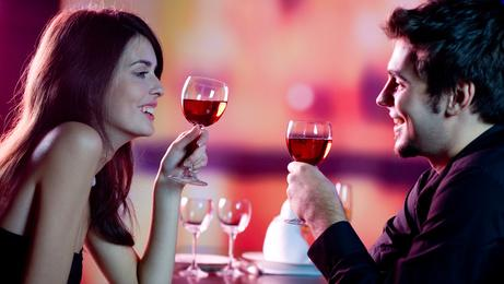 Young couple celebrating with red wine at restaurant - togethermedien.net