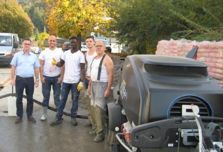 Ein erfolgreiches Team: Der EstrichBoy EC 350 mit Vater Bernd Laux, seinen Söhnen Sven und Lars sowie ihrem Mitarbeiter Ebou und Putzmeister Gebietsvertriebsleiter Mario Schlegel.