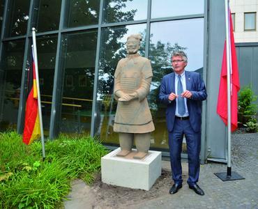 Prof. Dr. Gerd Schwandner, Oberbürgermeister a.D., präsentiert im Museumsgarten des Stadtmuseums Oldenburg die ihm zugedachte Ehrengabe – den Terrakottakrieger General Yuan (Bildquelle: Stadtmuseum Oldenburg)