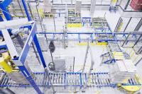 Die fertig kommissionierten Paletten werden zu einem Umwickler transportiert, der für die Ladungssicherung sorgt