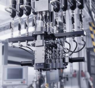 Das speziell für Votteler konzipierte Beschichtungssystem verfügt über einen Mischkopf für vier Komponenten. Daher können neben den beiden Lack-Grundbestandteilen, transparentes Polyol und Isocyanat, zwei weitere Komponenten zudosiert werden.  Bildquelle: Votteler Lackfabrik GmbH