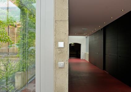 Verschiedene Werkstoffe harmonieren miteinander, wie hier Kunststoffschalter, Beton und edles Holz.