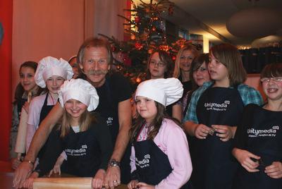 """Die elf Mädchen der Jugendeinrichtungen """"Boltensternstraße"""" und """"Take Five"""" freuen sich über das fröhliche Beisammensein mit Henning Krautmacher bei Unitymedia"""