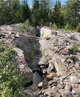 Foto 2: 80 m langer Graben auf dem Grundstück Rivard, Blick zurück entlang des Streichs einer goldhaltigen Ader